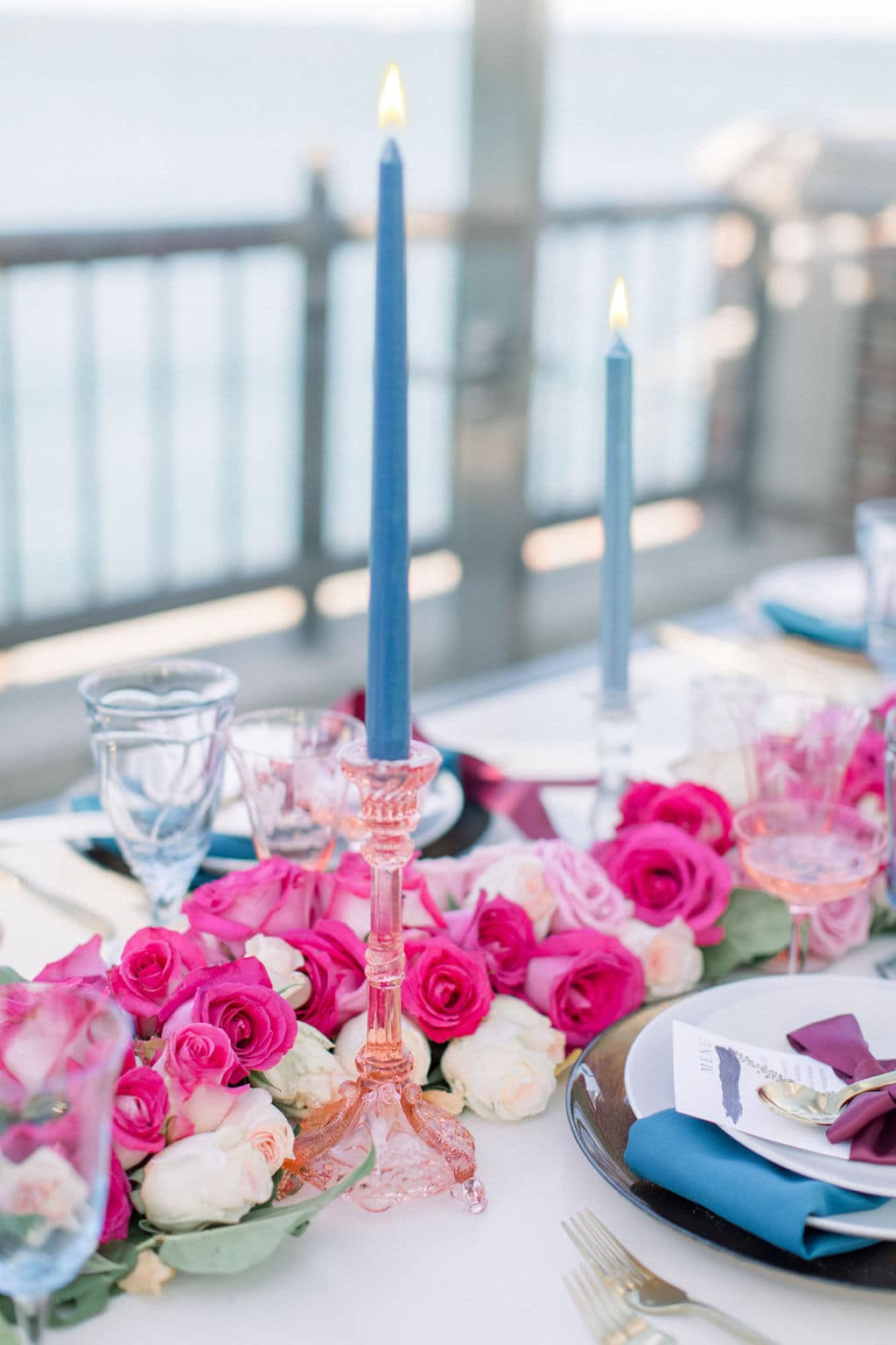 blue and pink glassware at table with pink roses
