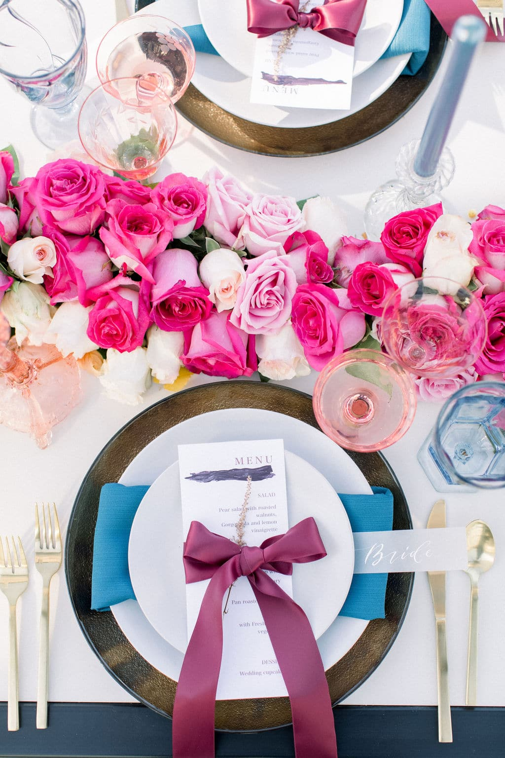 further shot of table setting that shows off pink rose centerpiece