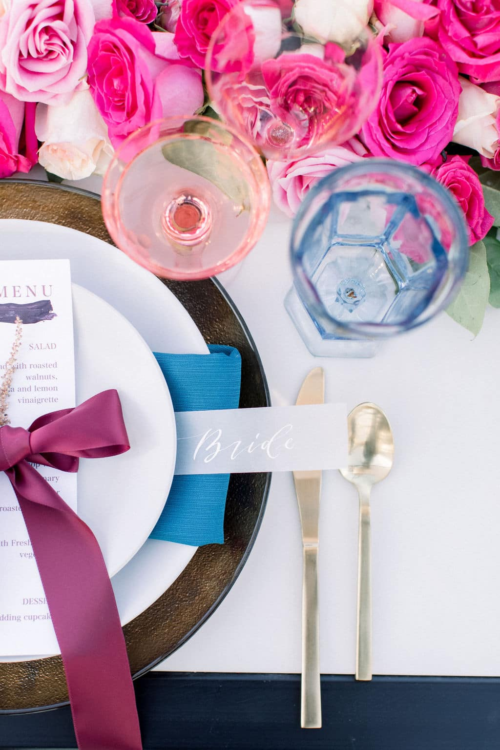 blue glass with blue and purple table setting with custom name tag that says bride