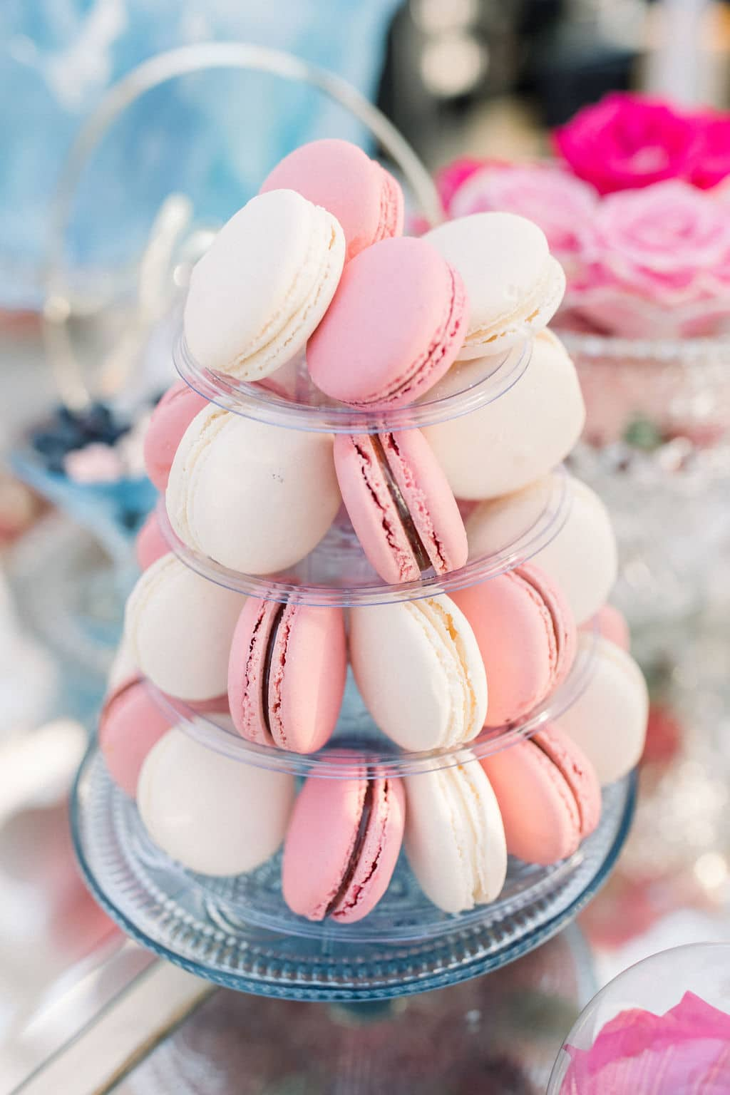 pink and whit macaroons on a beautiful four tiered tray for wedding guests