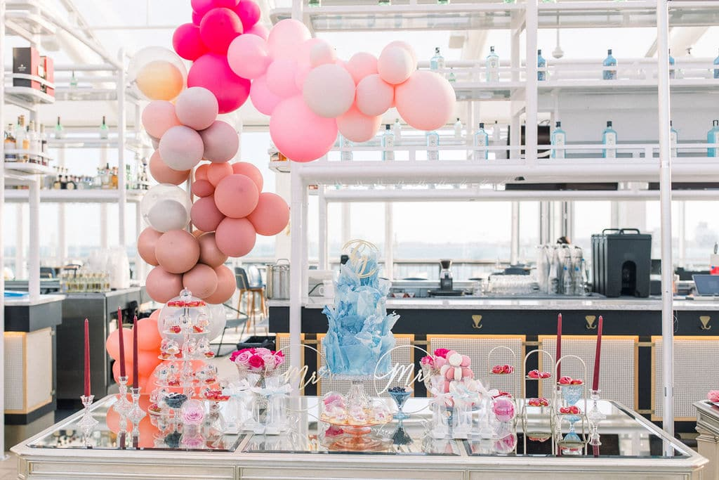 the array of drinks and food and pink balloons accent the wedding venue