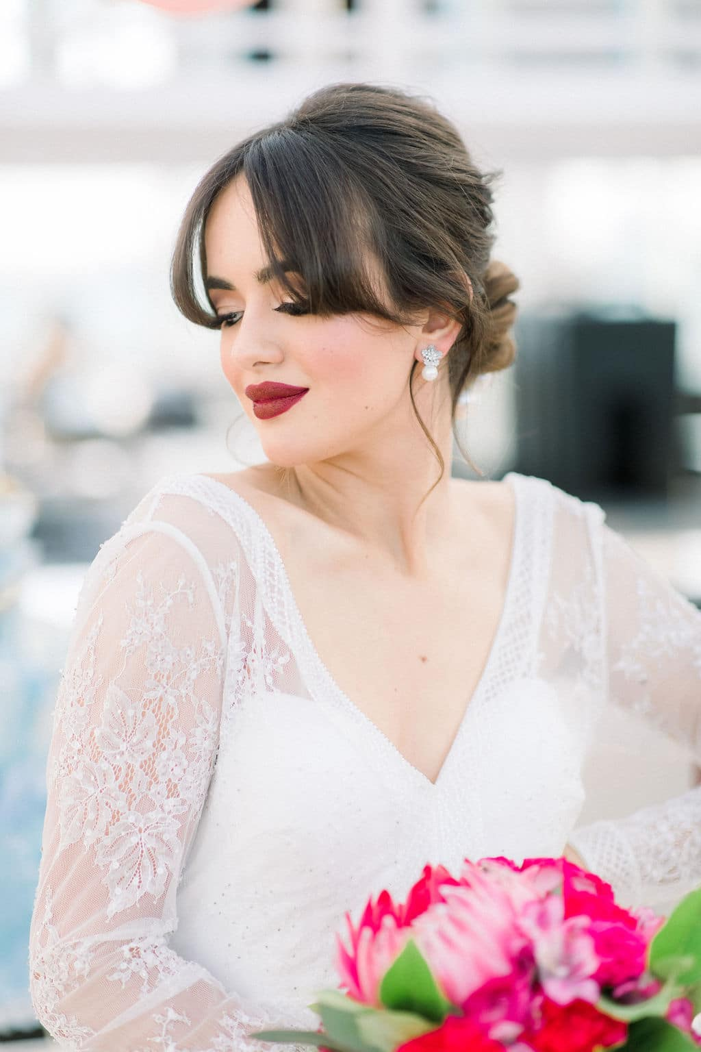 bride with bright red lipstick and pink roses
