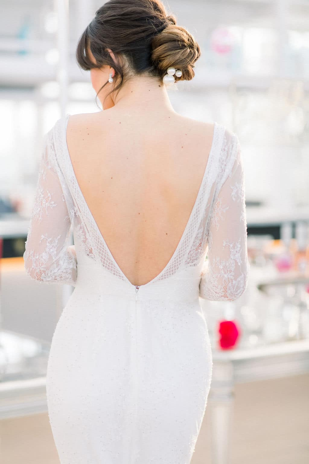 the back of the white lace wedding dress with a low back and long sleeves
