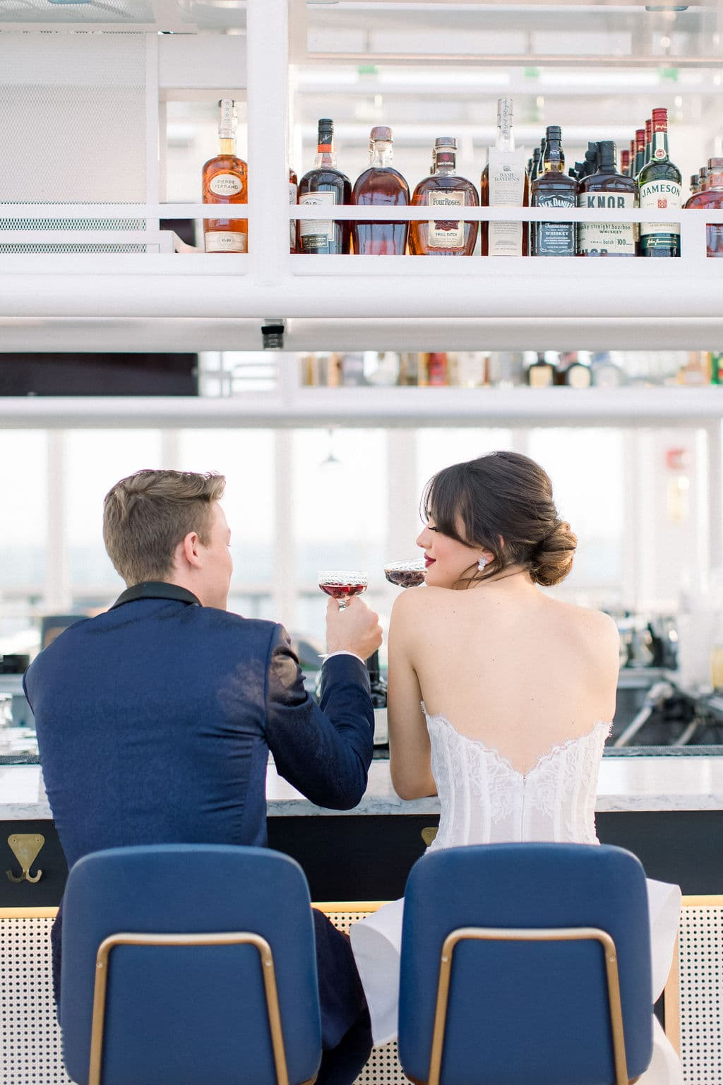 the bride and groom sitting at the bar of the wedding venue having a little cheers