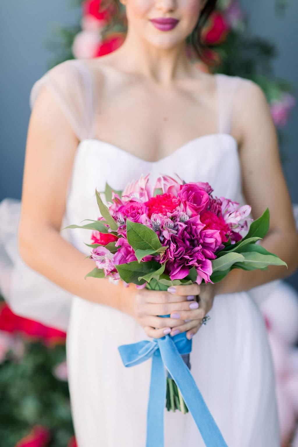 bride closeup of red lipstick and bright pink rose bouquet
