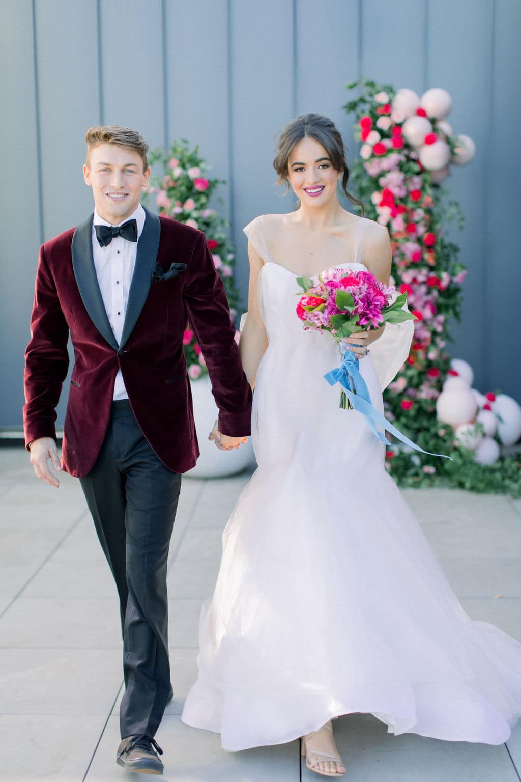 groom and bride walking and the bride's bouquet is fully shown with pink roses and a blue ribbon