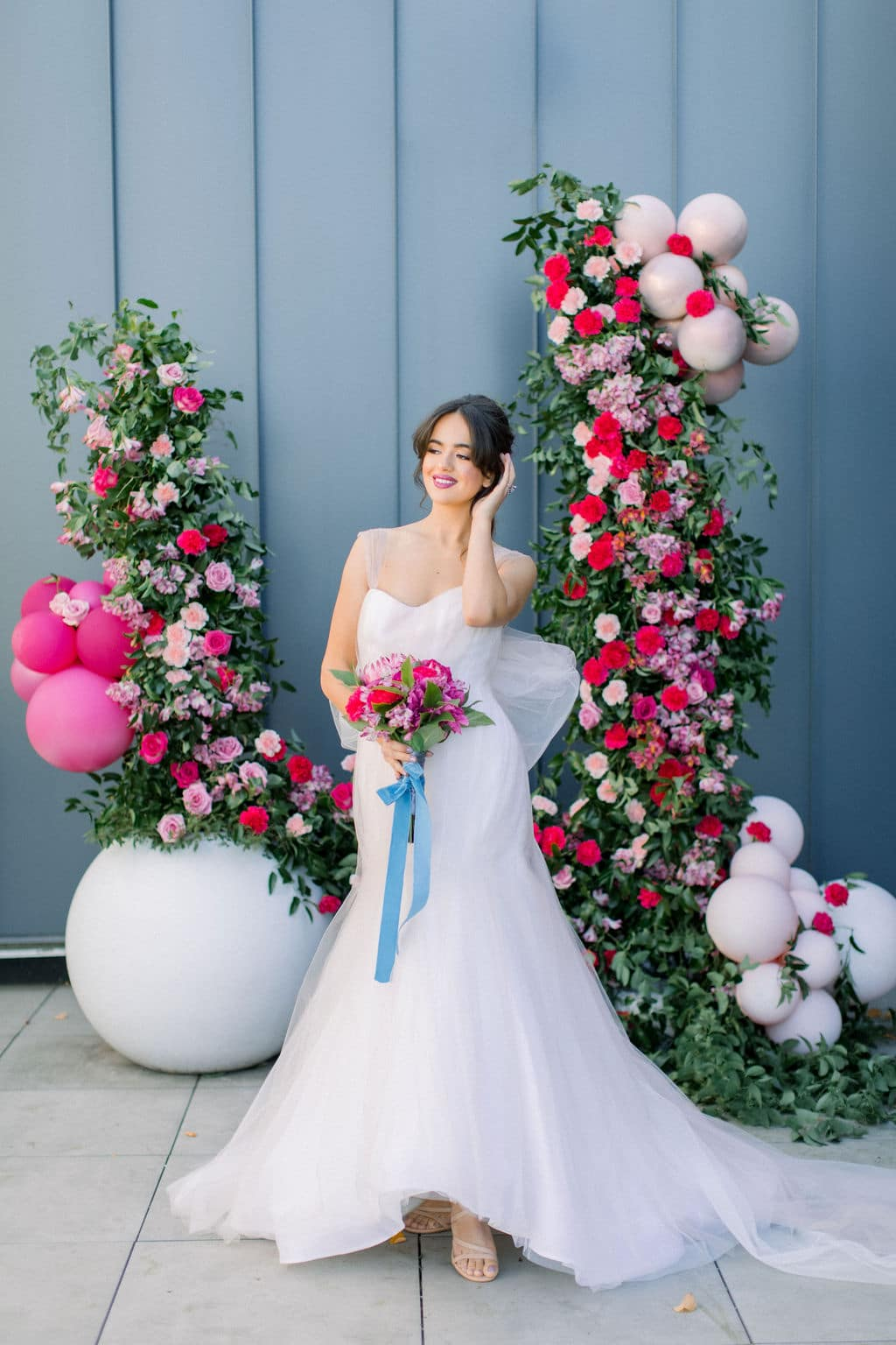 baloons and pink and purple flowers behind bride in mermaid gown