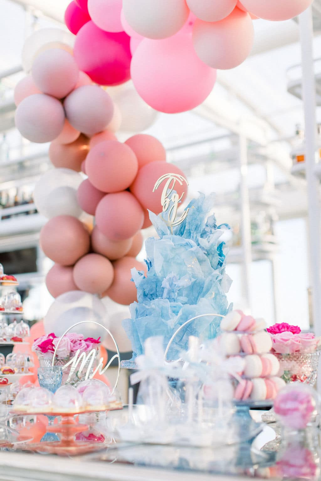 blue floral wedding cake surrounded by pink wedding balloons