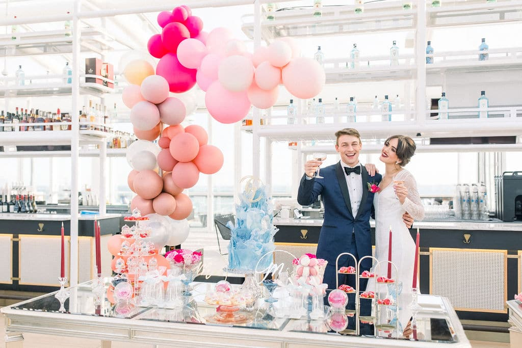 cheers from the bride and groom with champagne and pink balloons all around them