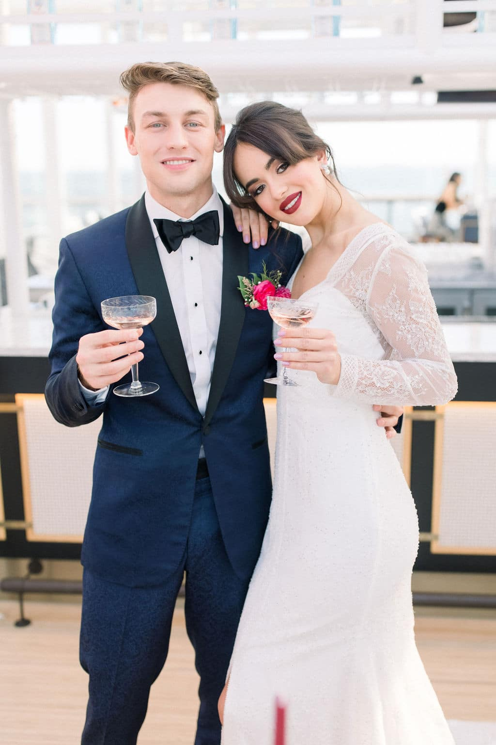 bride and groom posing with champagne and the bride has red lipstick