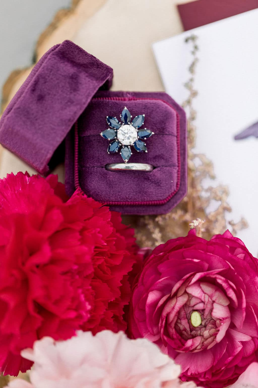 blue and white diamond ring in purple box surrounded by red and pink roses