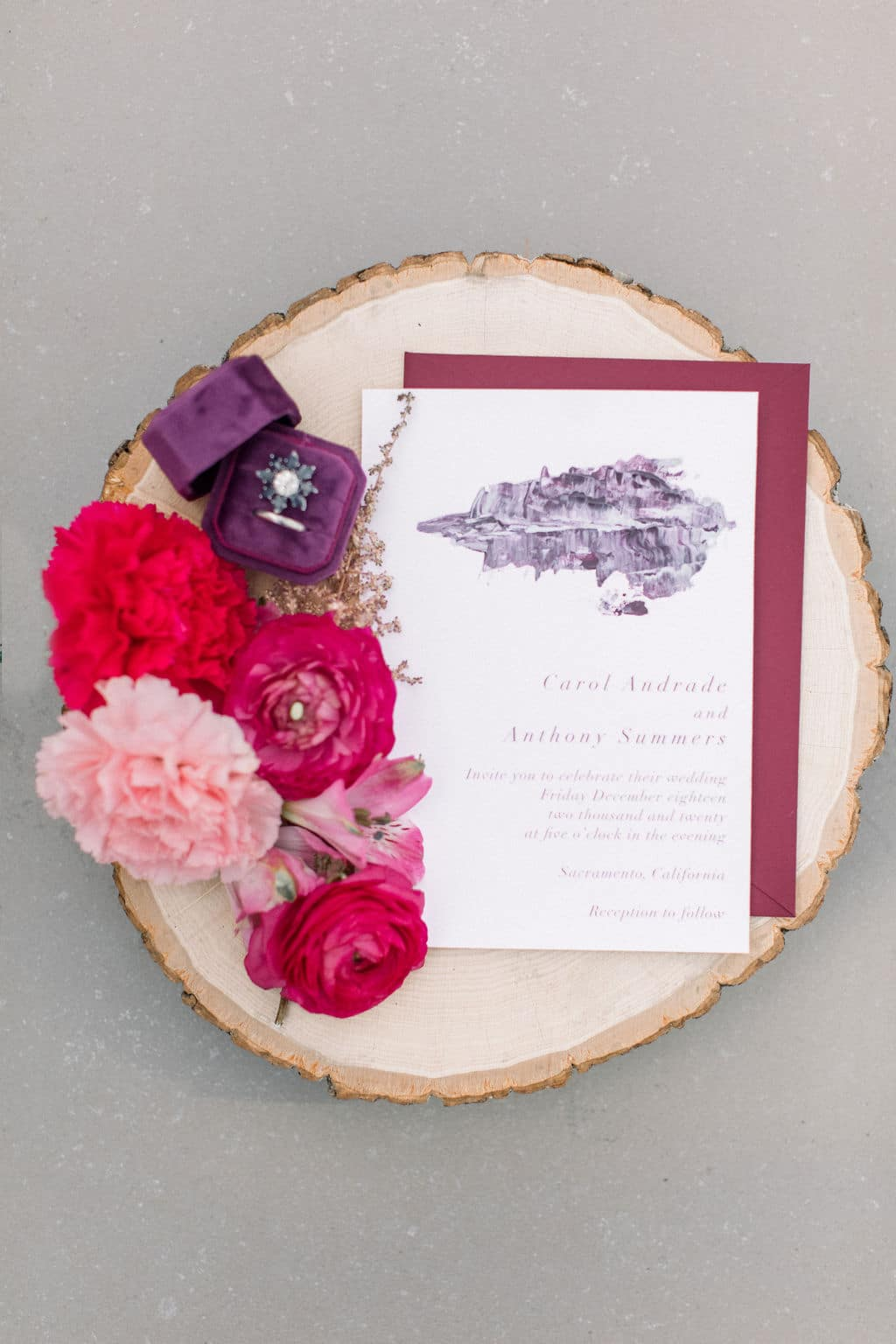 red and purple wedding invitation on round wooden tray