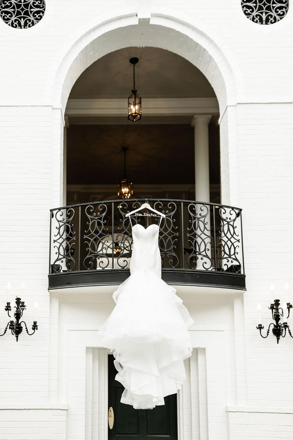 bride's gown hanging on a hanger off a gorgeous balcony of a white rustic building