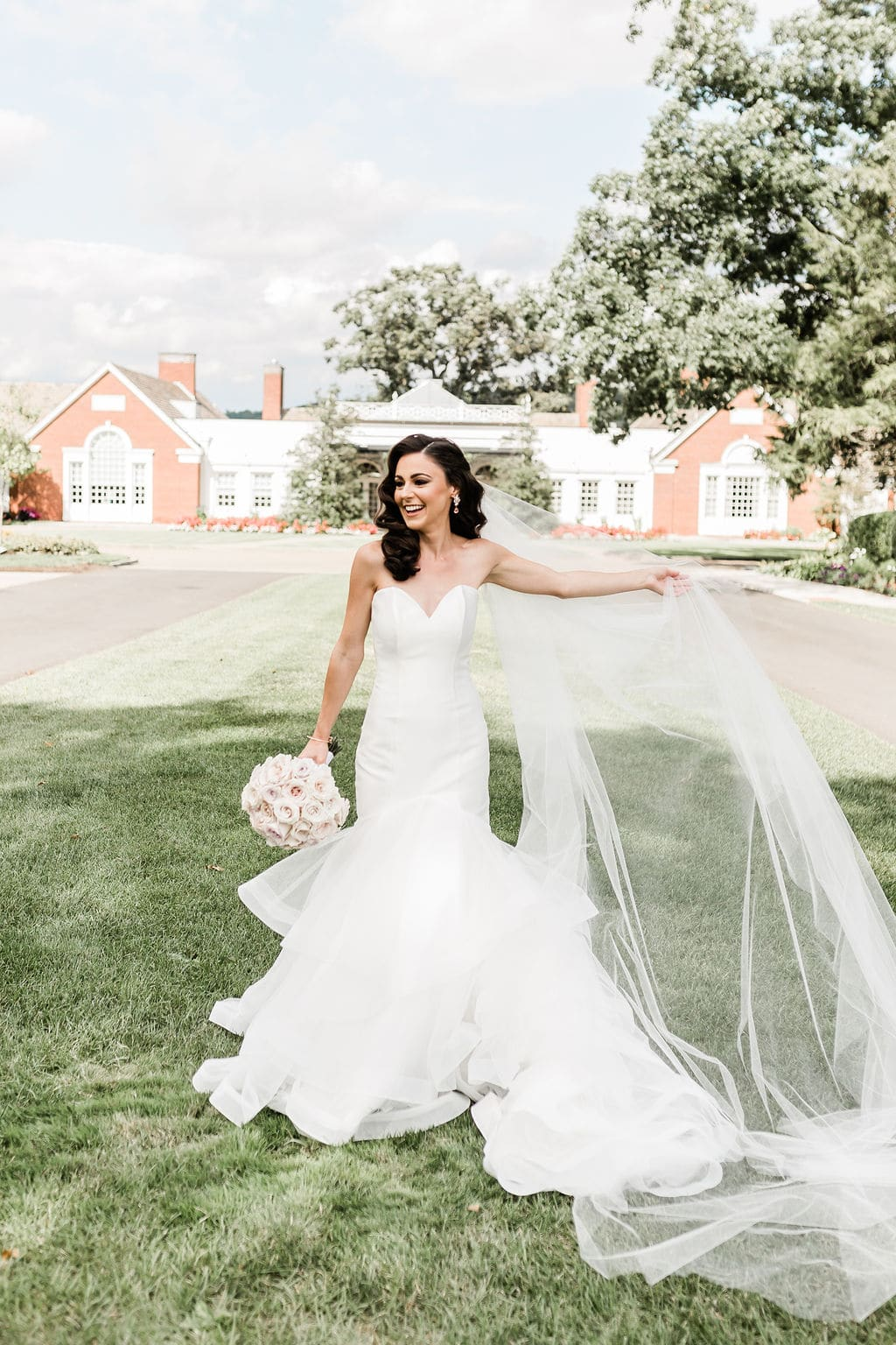 bride smiling holding veil in front of rustic building