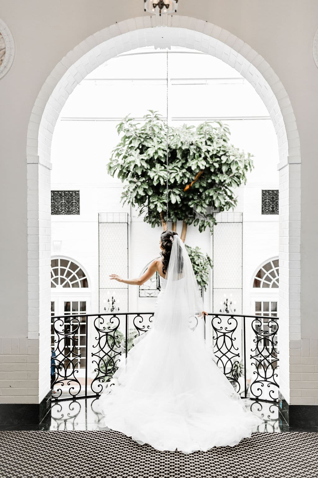 back of bride in front of large window with greenery