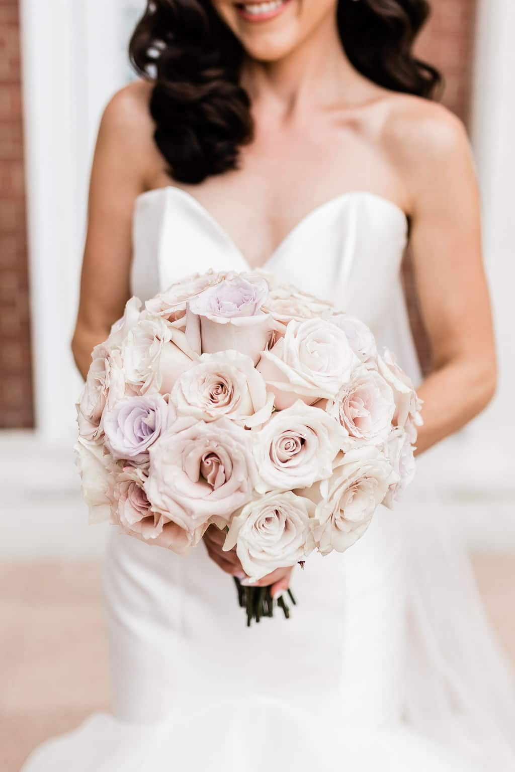 bride smilinng holding beautiful blush pink bouquet of flowers