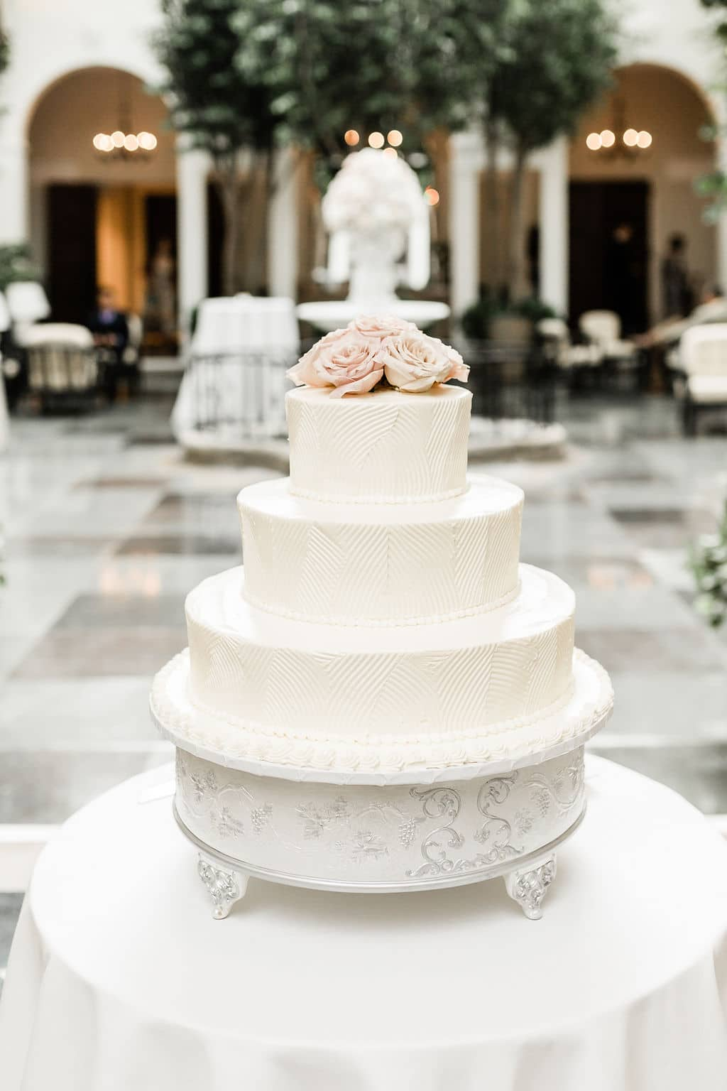 white wedding cake with blush pink flowers on top