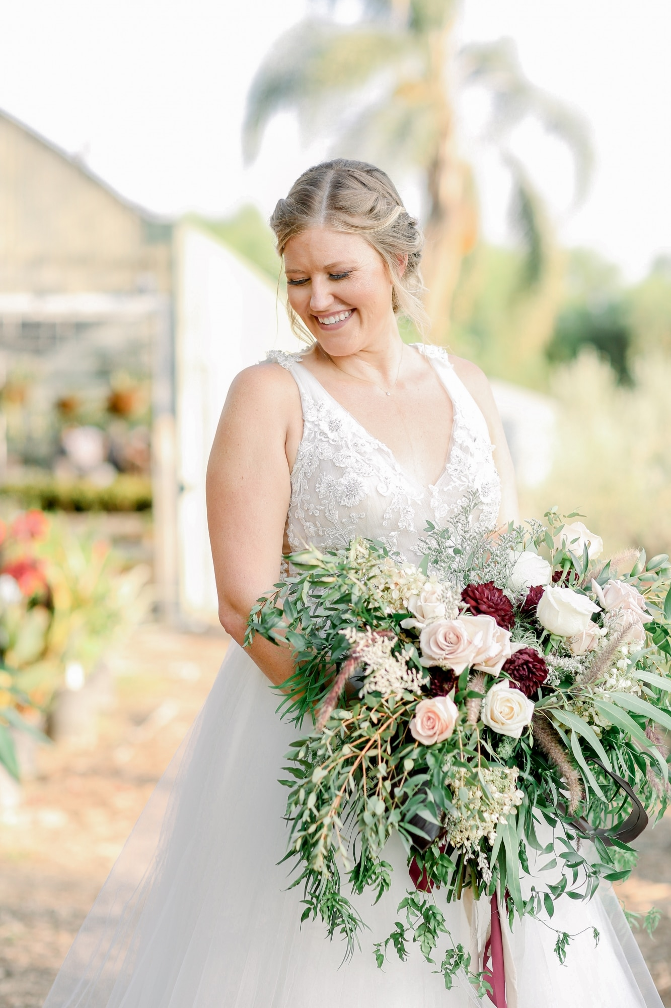 bride looking down holding beautiful bouquet with red and white roses