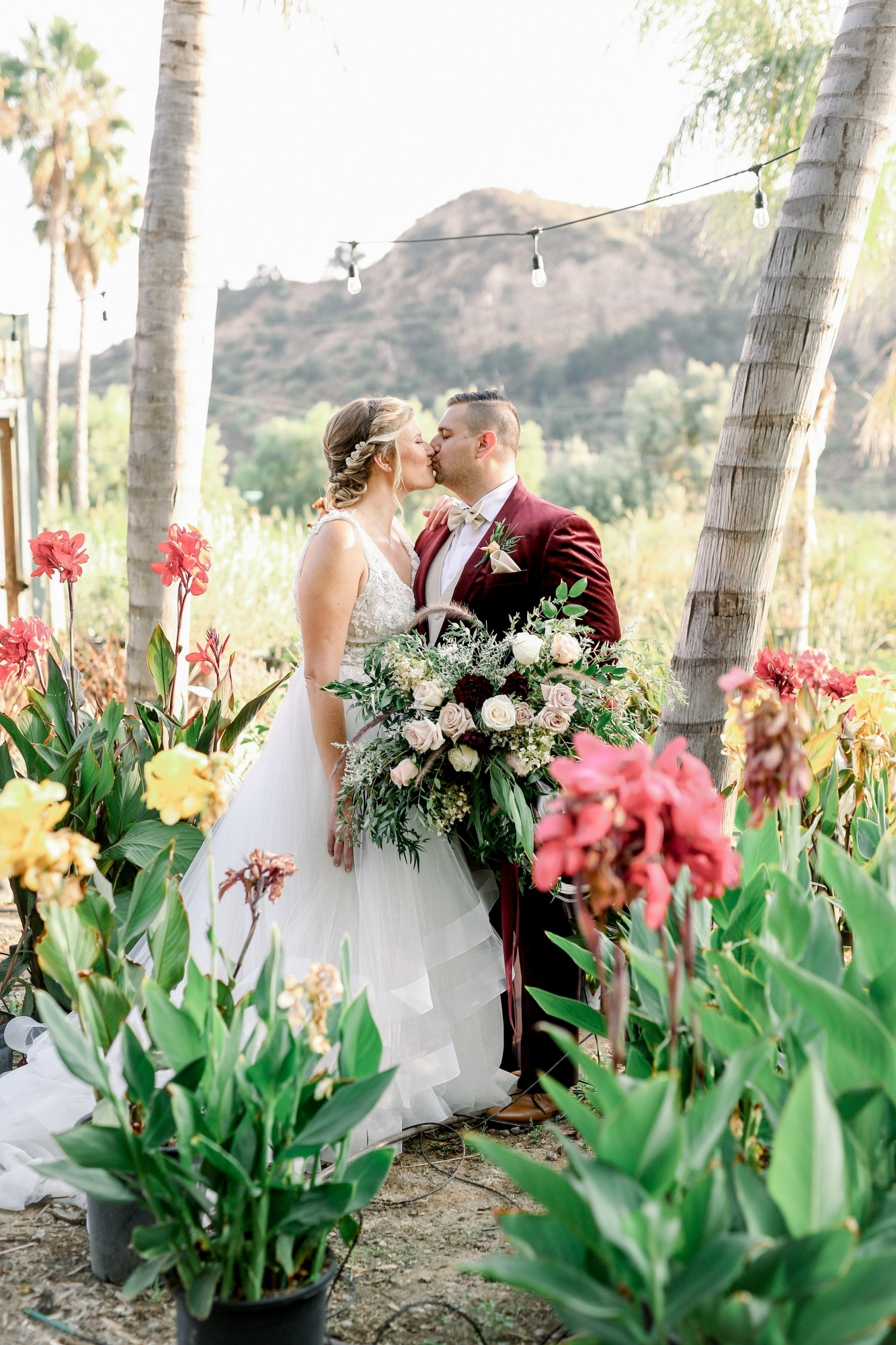 bride and groom kissing in the middle of a garden