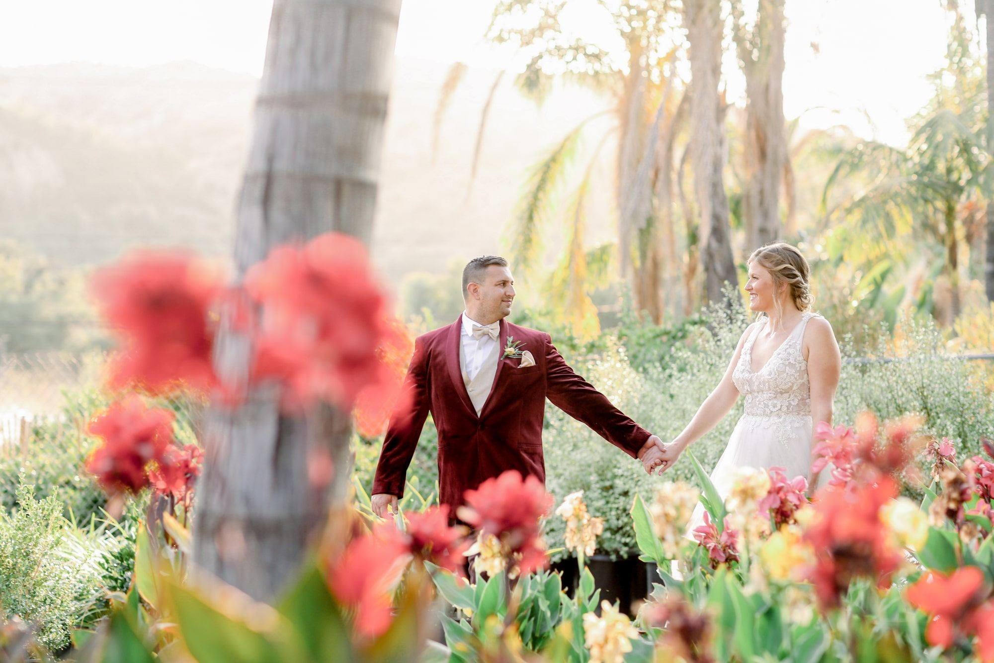 bride and groom in garden tucked behind some pink flowers holding hands