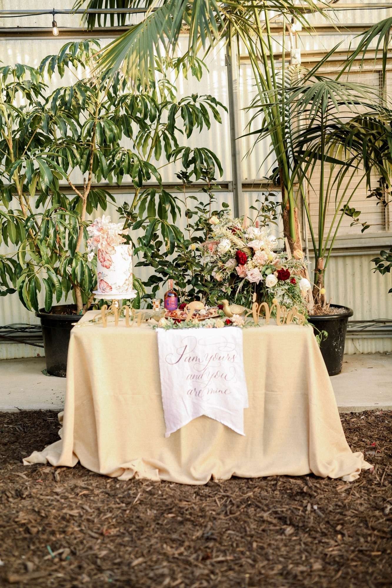 cream table cloth with pink and white floral wedding cake on top