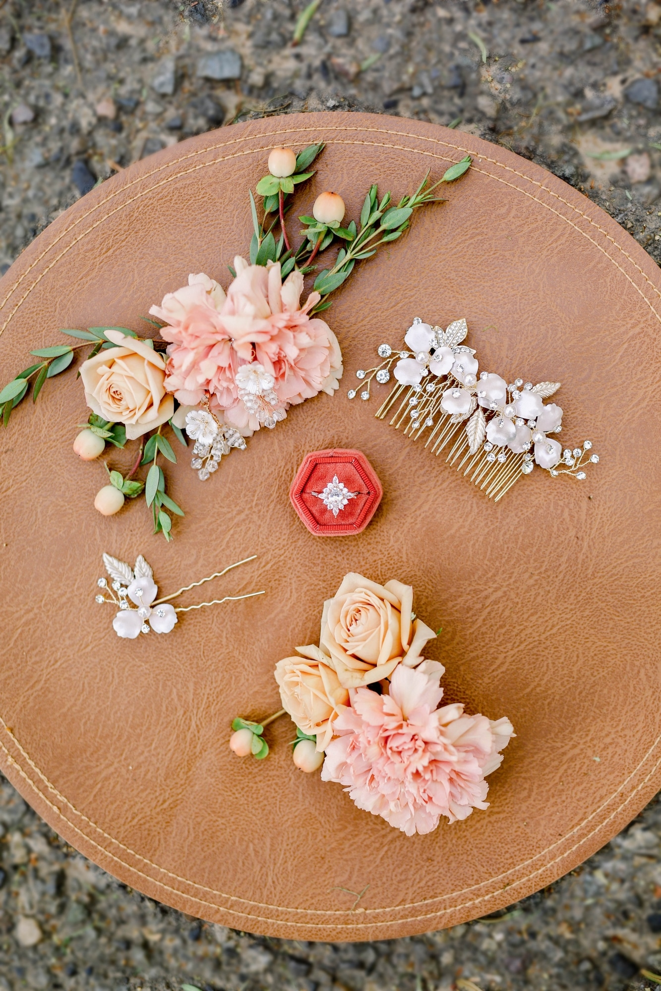 bride's accessories with ring in red box and roses around it