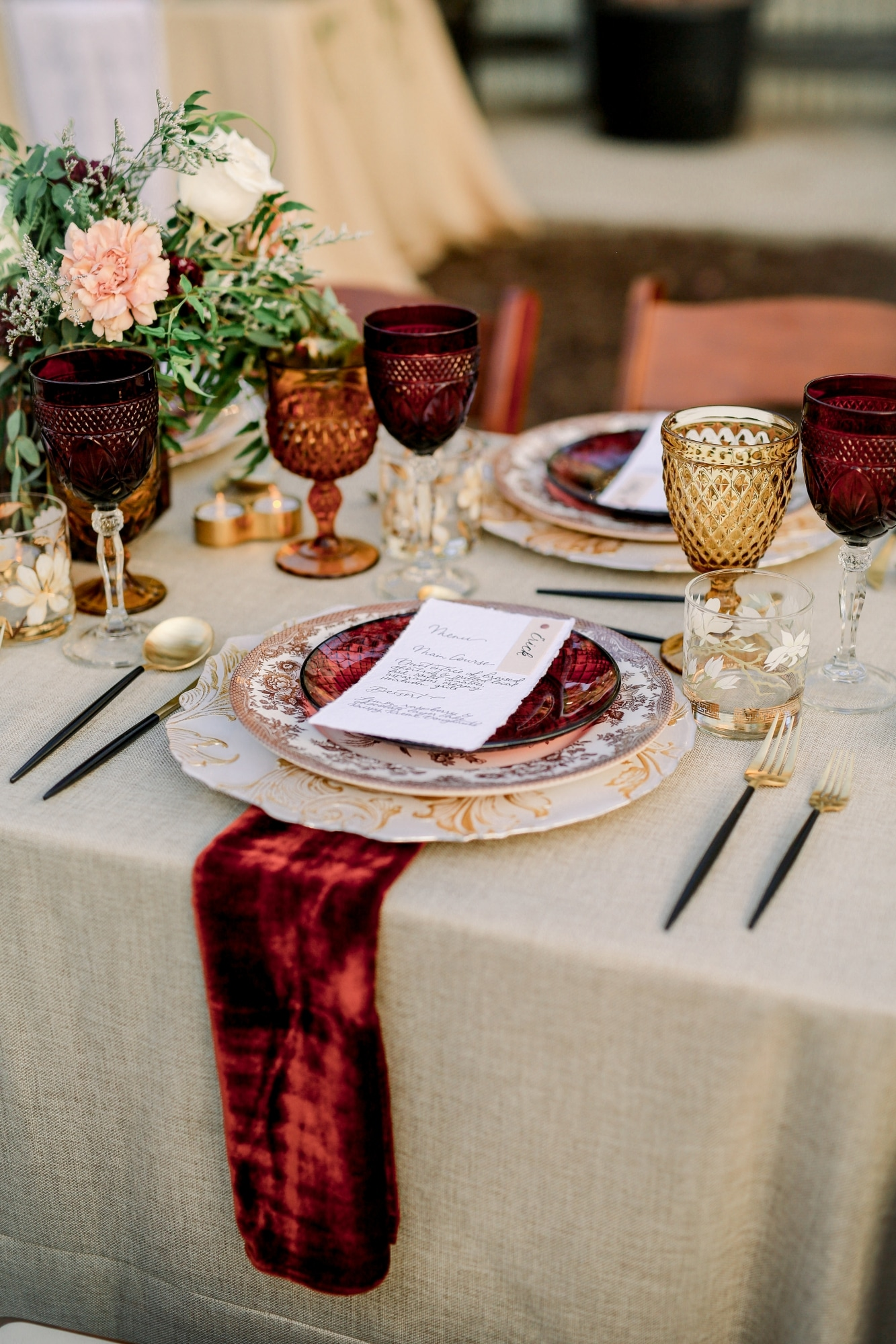 red velvet table runner with many and different colored glasses