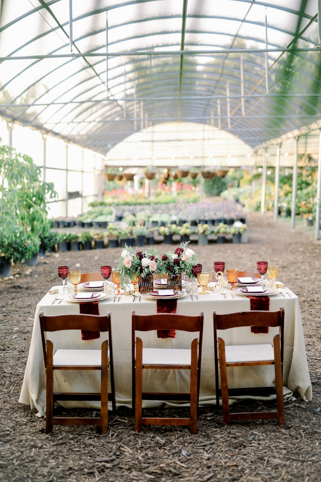 green house wedding garden venue with rustic wooden chairs and table set