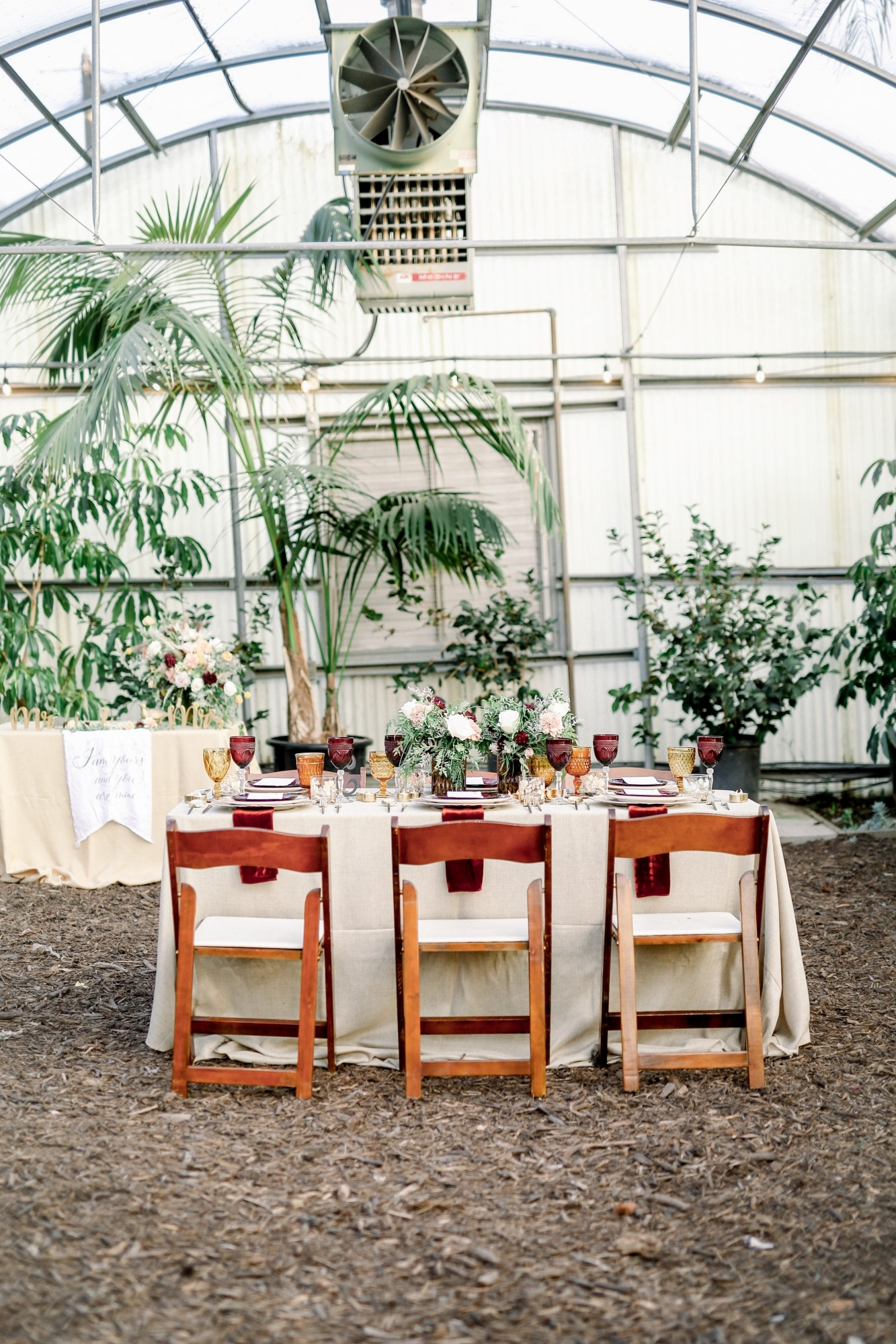 garden wedding table set with red glasses