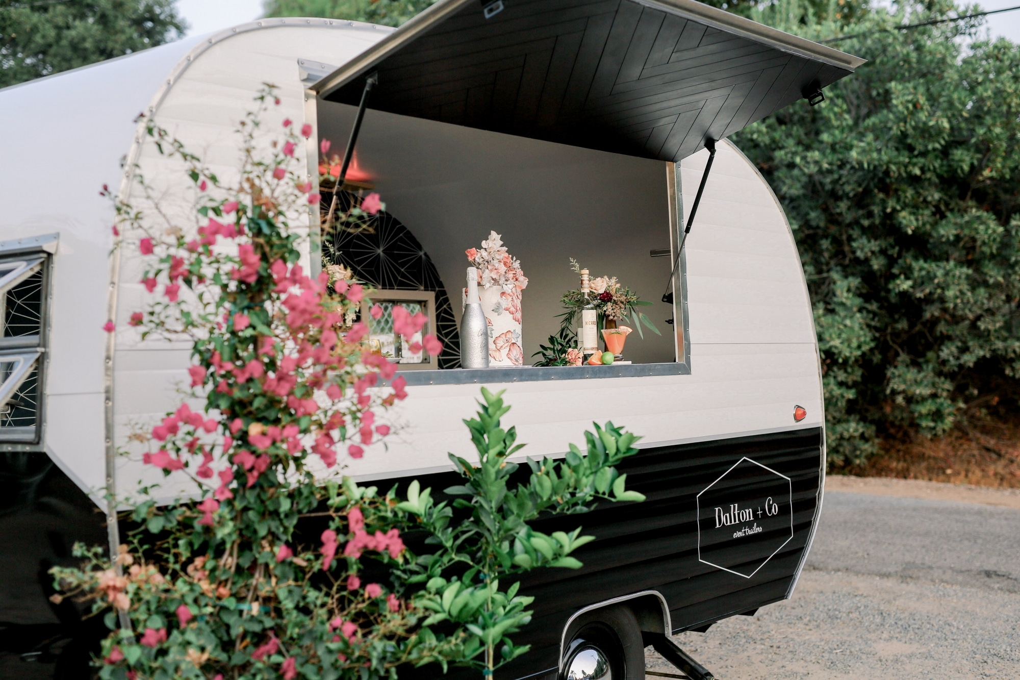 pink flowers in front of restored antique camper with wedding cake in it