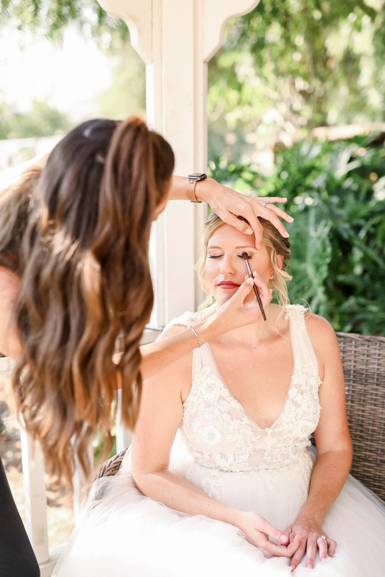 bride with red lipstick getting makeup done
