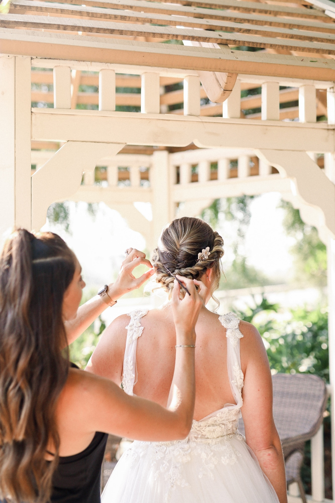 bride getting her hair done in the white gazebo in an updo