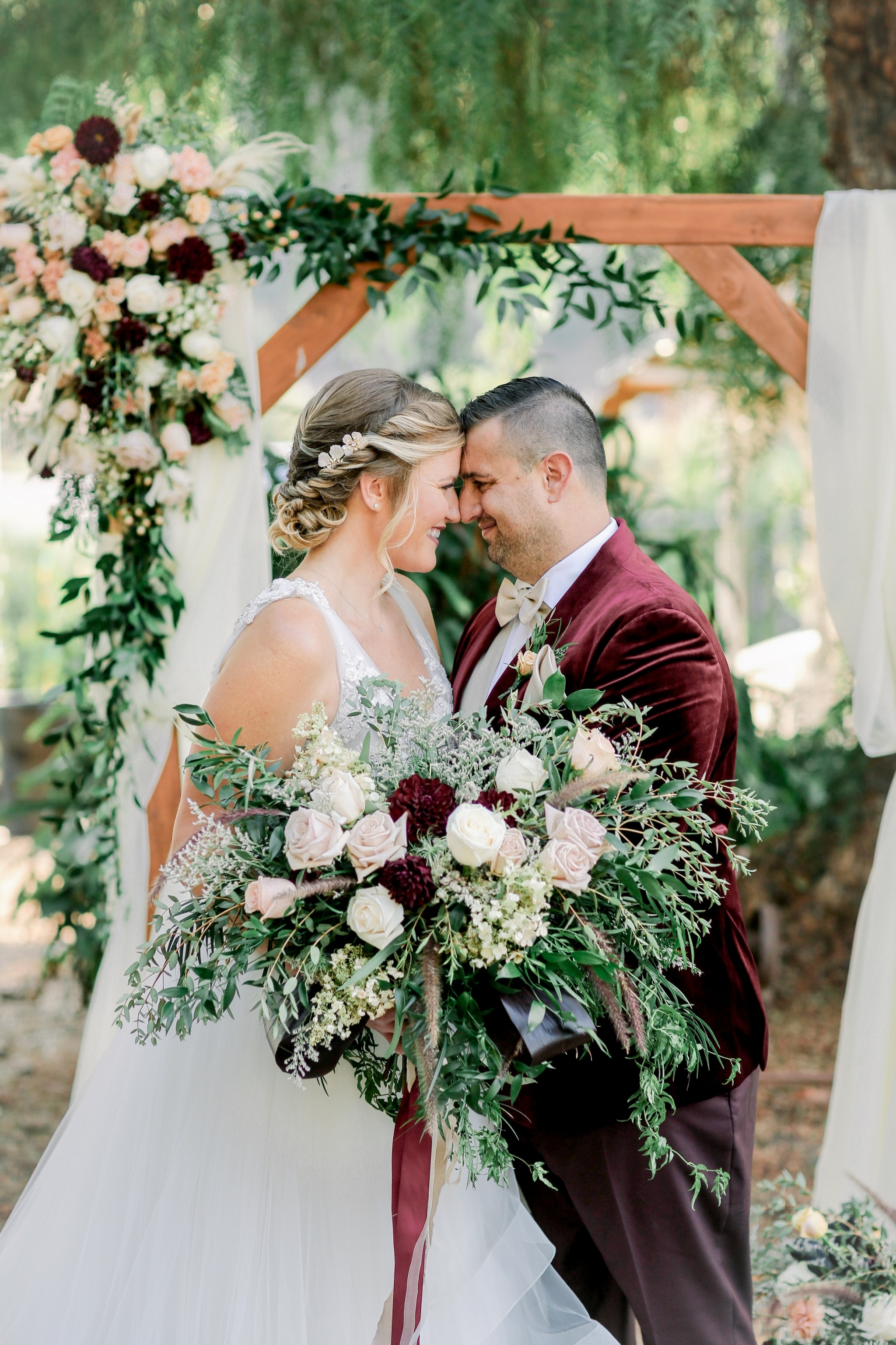 bride and groom touching noses with bride's bouquet in her hands where the ceremony was