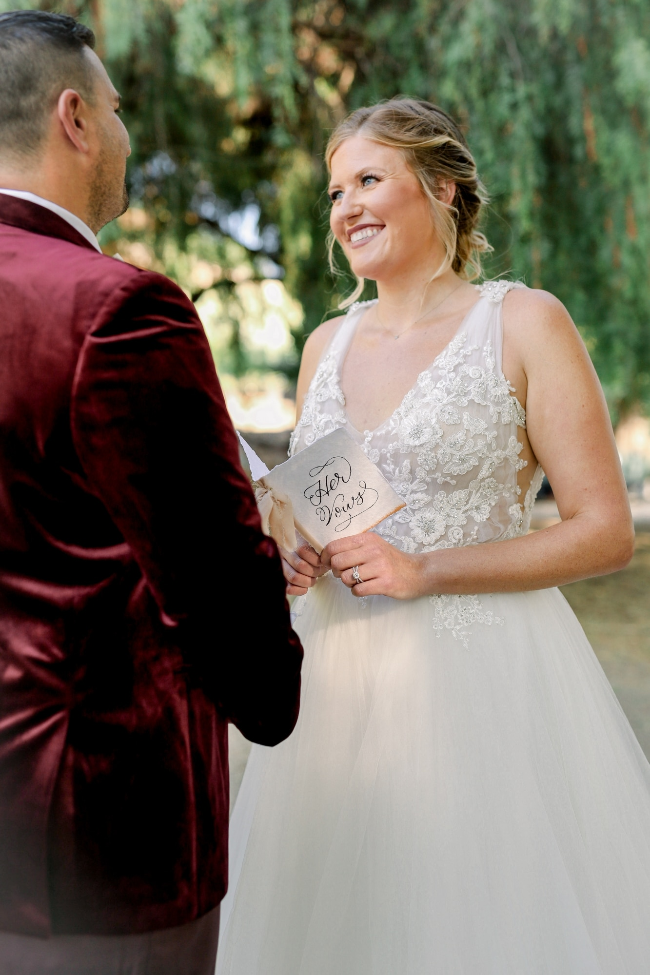 bride smiling at groom with up do for her hair