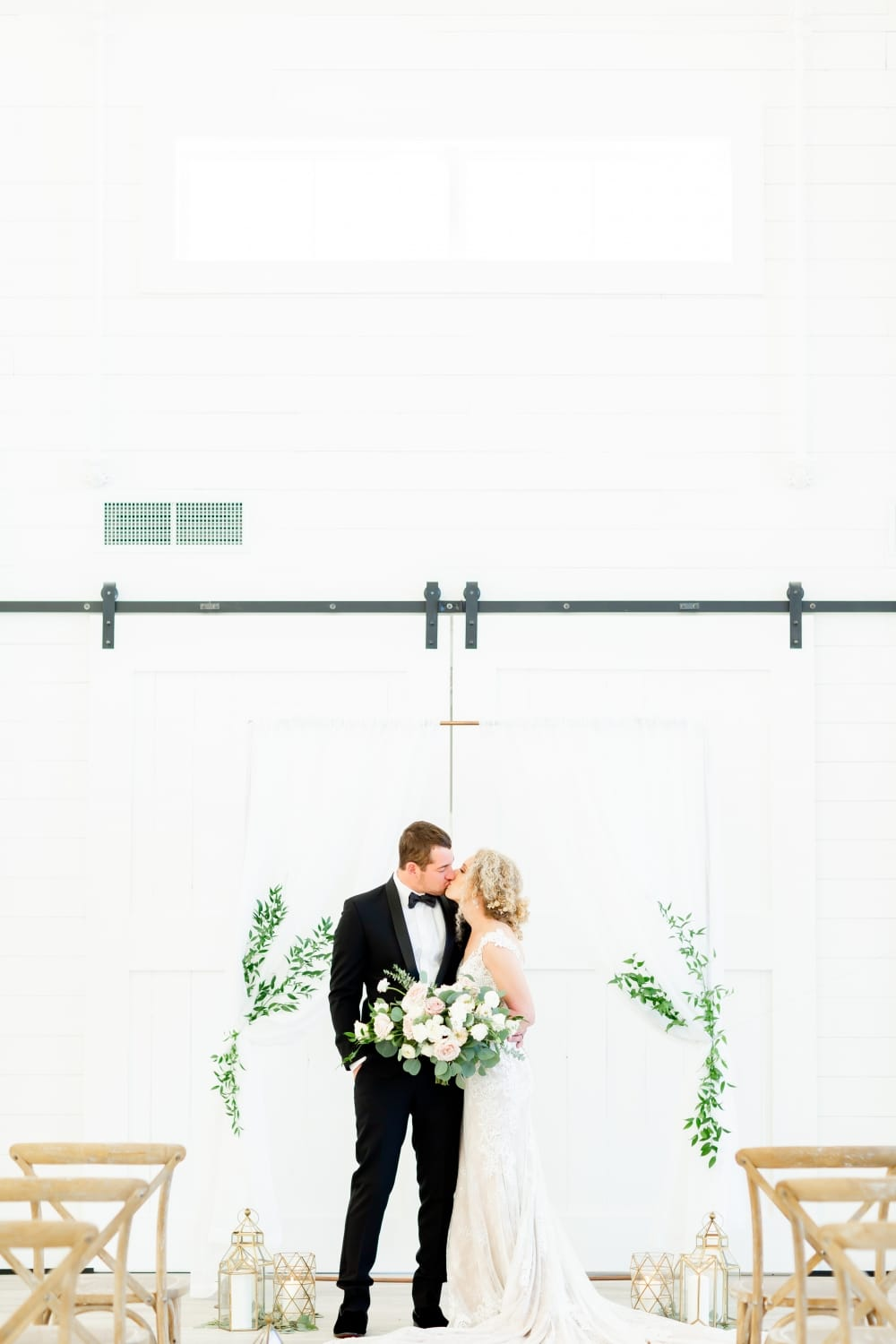beautiful white barn grand doors with kissing wedded couple in front with boho decor