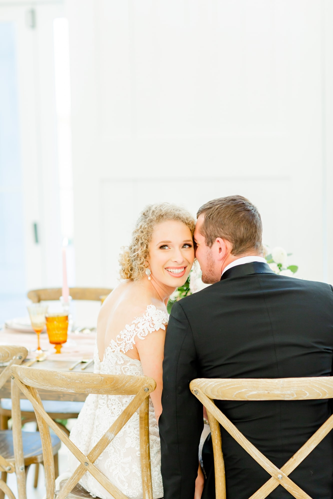 bride kissing smiling bride who is looking back at camera in rustic wooden chairs