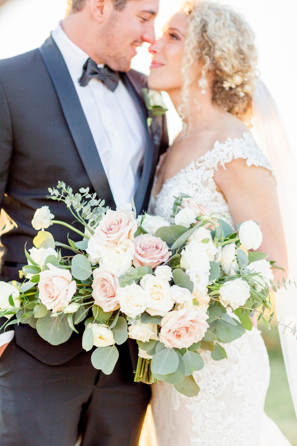 closeup detail shot of rose bouquet with bride in white lace dress