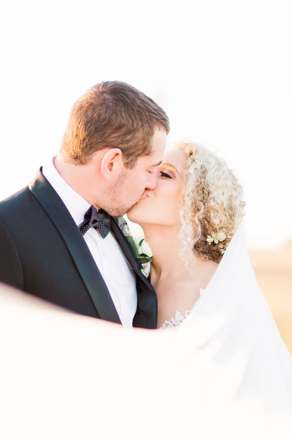 groom and bride kissing closeup with bride updo