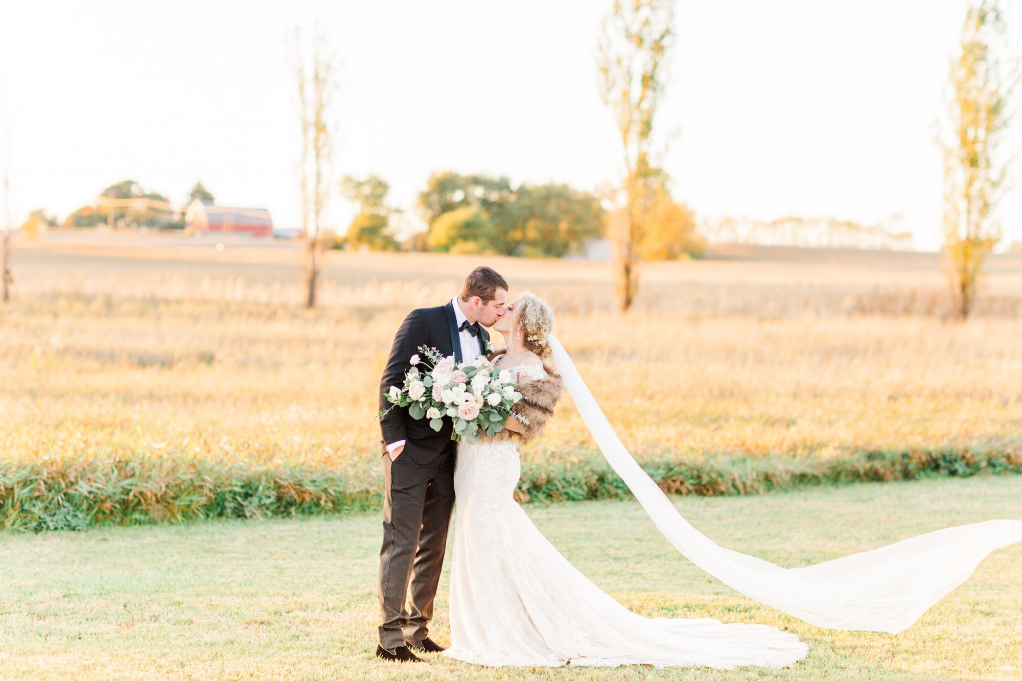 bride veil in wind as wedded couple kiss in fall farm white barn wedding