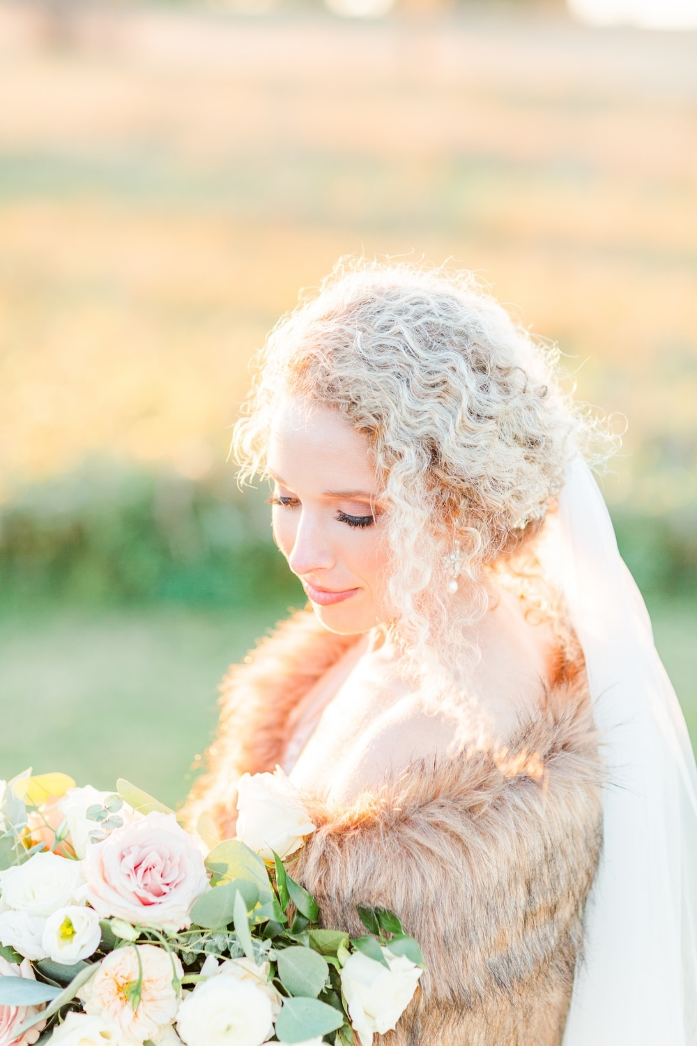 close up of bride looking down with lace veil and fall wedding