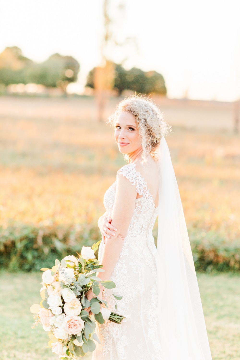 fall wedding with bride in lace gown and white rose bouquet