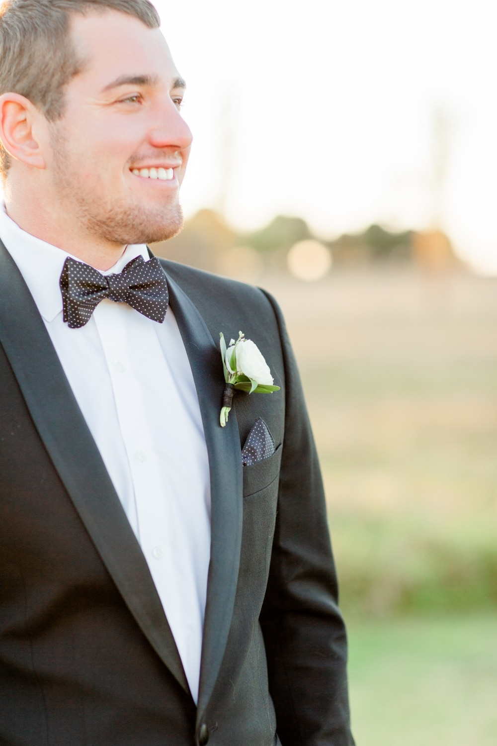 groom smiling in black tuxedo with white rose boutonniere