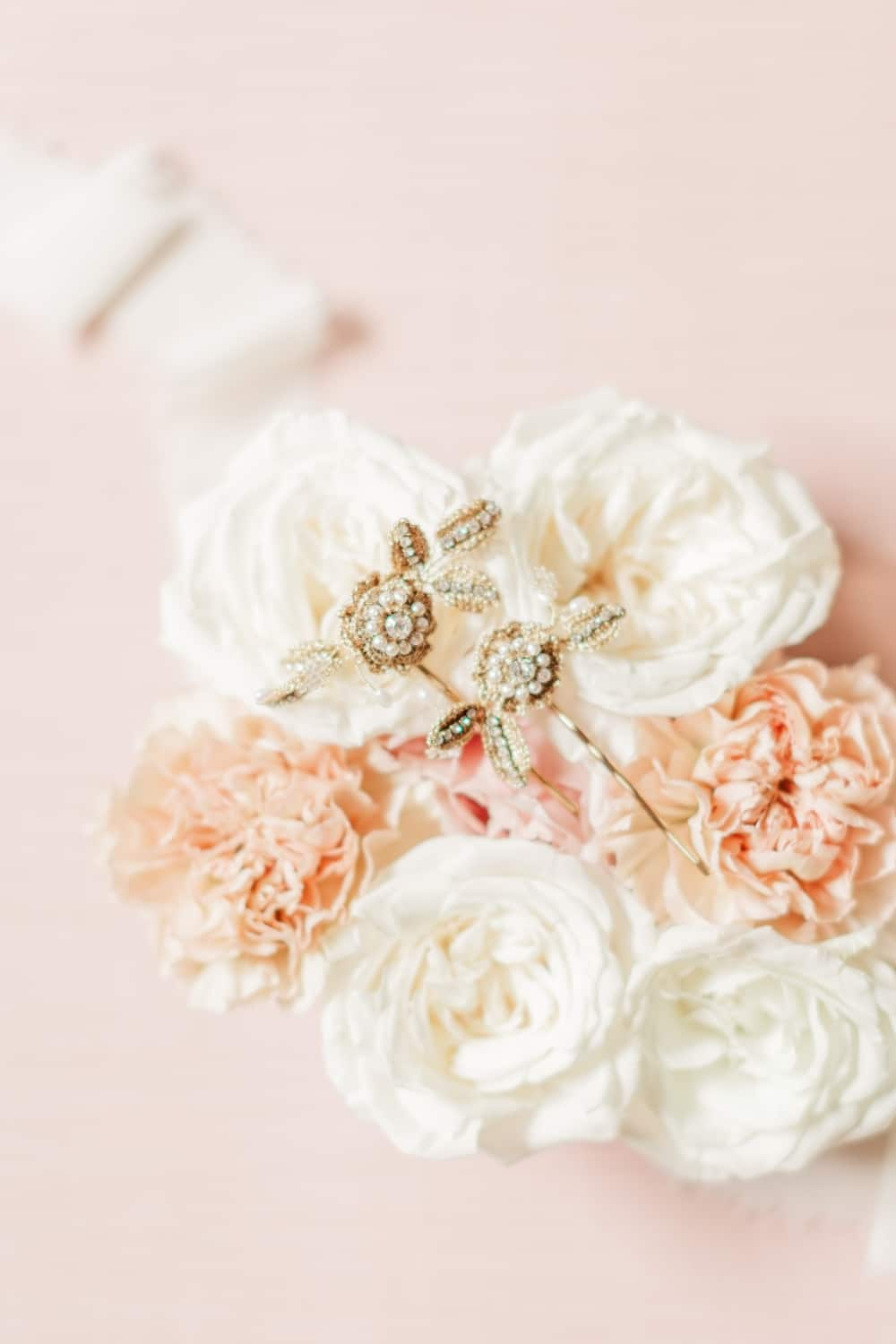 white and pink roses with bridal gold and sparkly jewelry