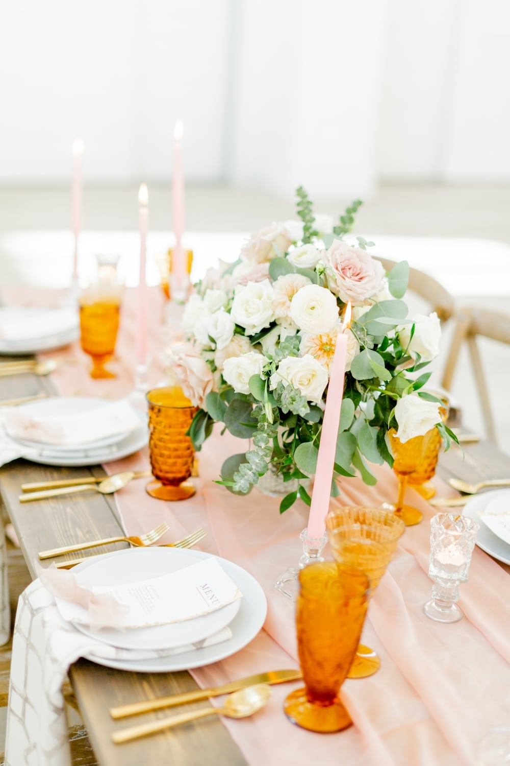 orange glasses and rose centerpiece as table setting