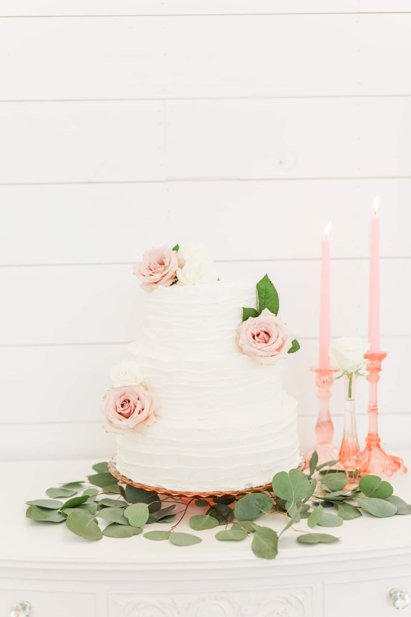 white wedding cake on stand with greenery and floral design on cake