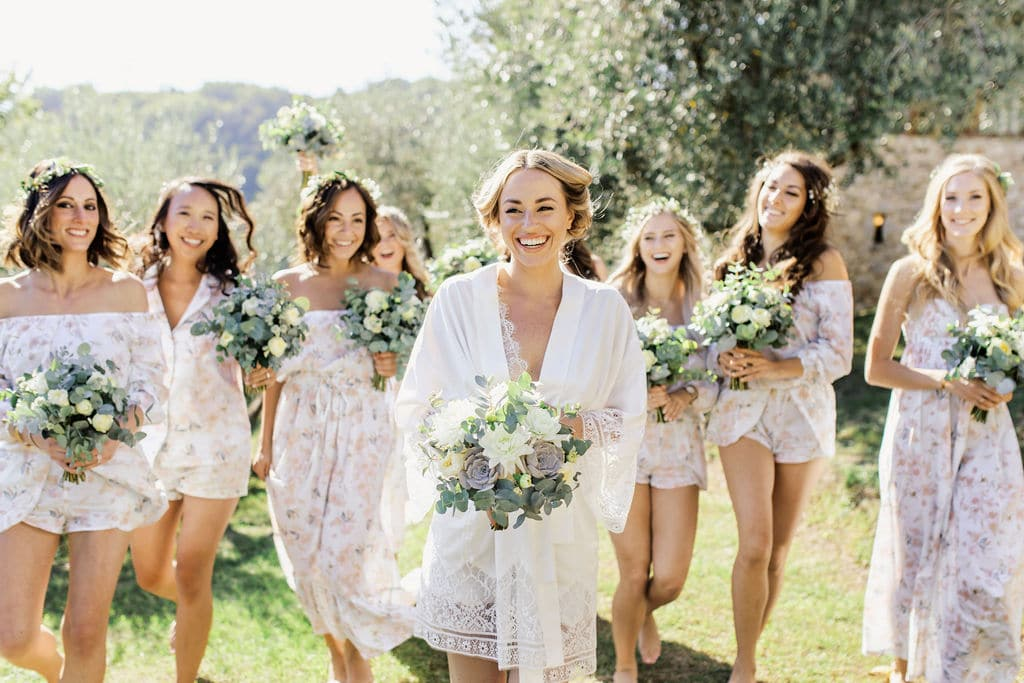 bridal party in short lace dresses getting ready for wedding laughing