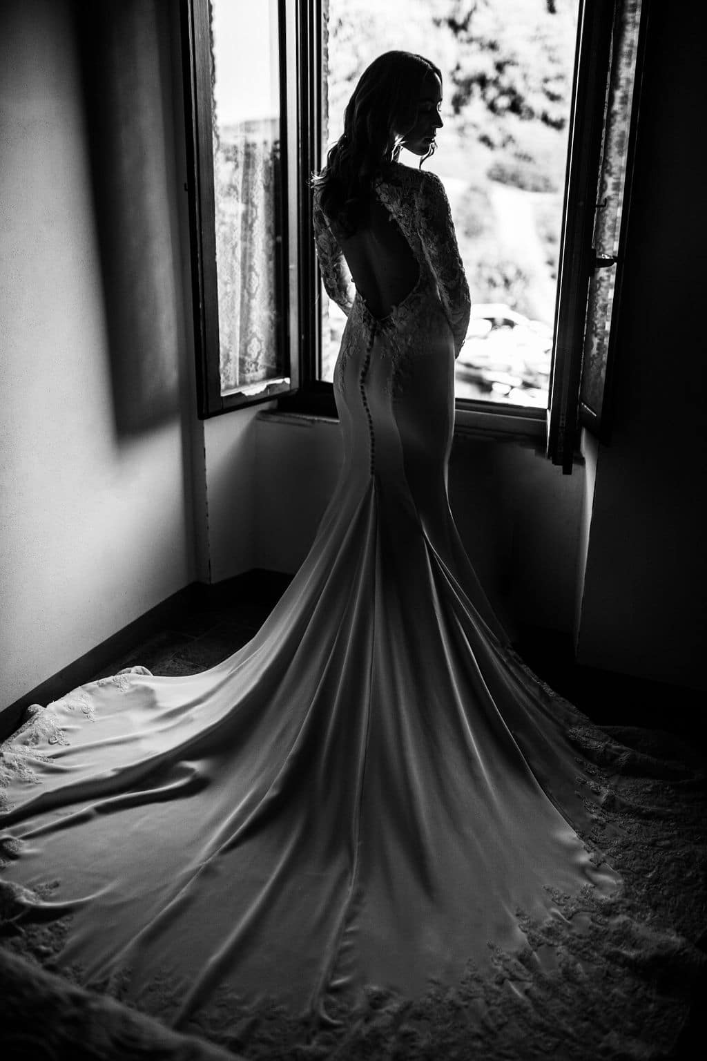 black and white shot of bride in gown in front of large window