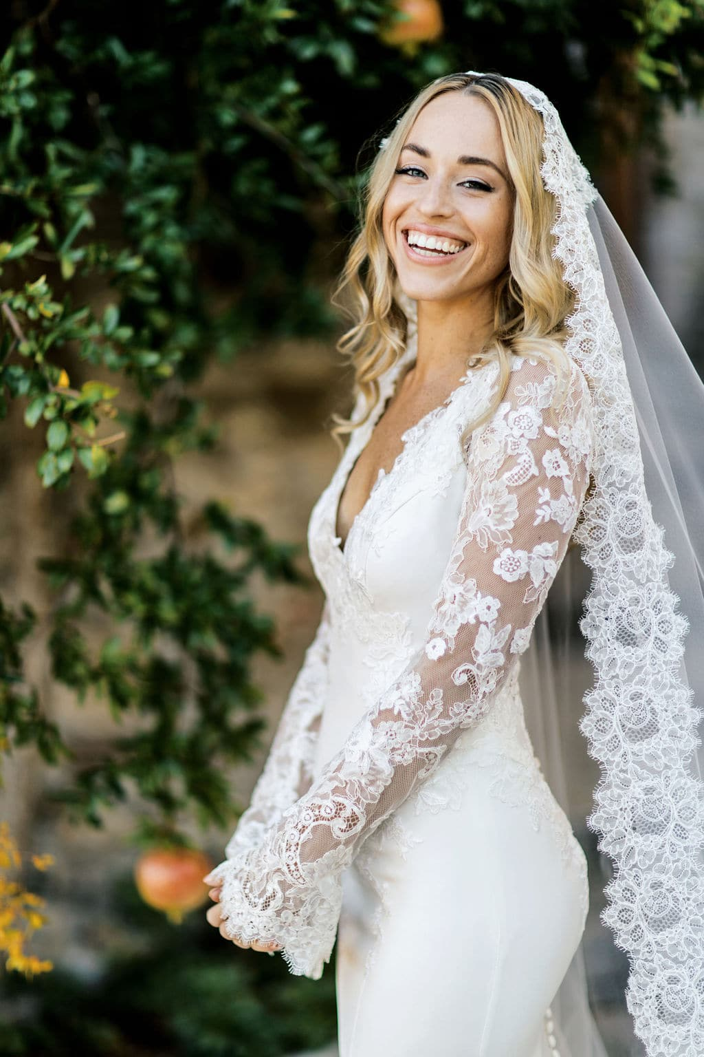 smiling bride with lace long sleeve form fitting gown
