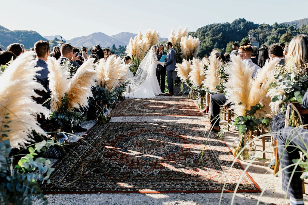 boho feathered plants decorated with boho carpet leading to ceremony