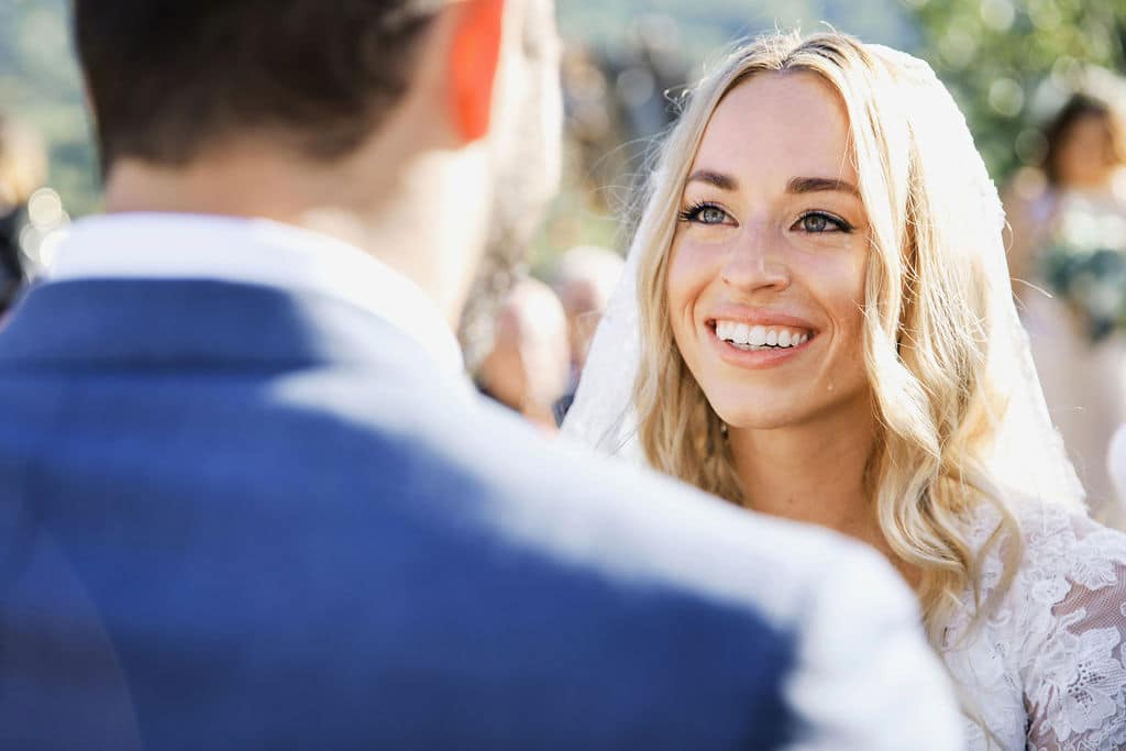 bride smiling at groom close up during ceremony